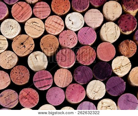 Natural Background Of Wooden Plugs In Different Shades And Colors. Top View Of Bottle Caps With Red