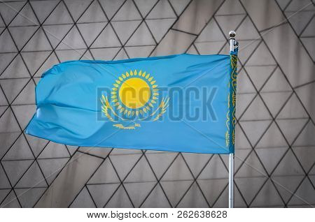 The Official Flag Of The Republic Of Kazakhstan Waving In The Sky Against A Triangles Background. Ka