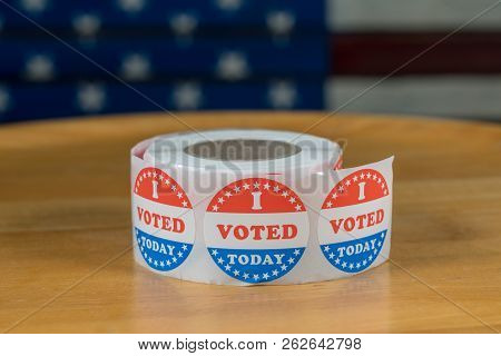 Large roll of I Voted Today stickers ready for voters in the US elections with flag in background poster