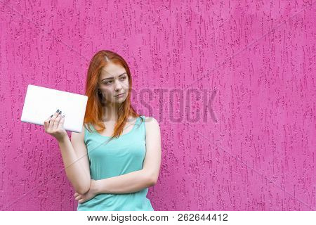 Portrait Of Young Happy Red Hair Girl Holding Tablet Pc Isolated On Pink Background. Woman Holding T