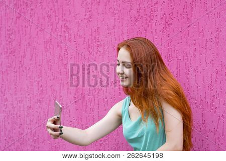 Waist-up Portrait Of Young Good-looking Model Taking Selfie And Standing On Pink Background. Fun Lif