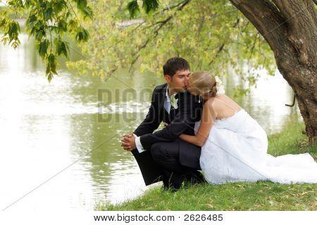 Newlywed Couple Kissing By Lake