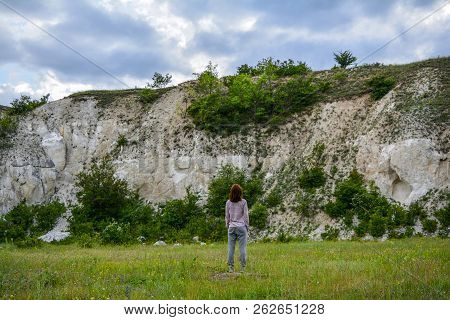 A Tourist Girl Looks At A Chalky Mountain, Admiring The View N The Evening At Sunset. A Mountain, Li