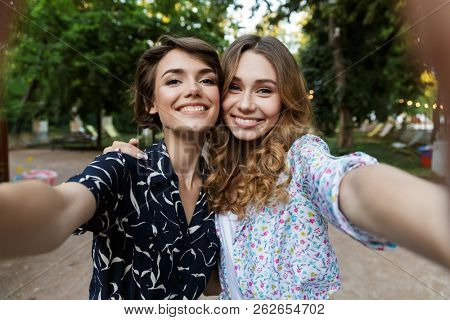 Image of happy young women friends outdoors in park having fun looking camera take a selfie.