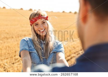 Photo of happy young cute loving couple standing on the field walking outoors.