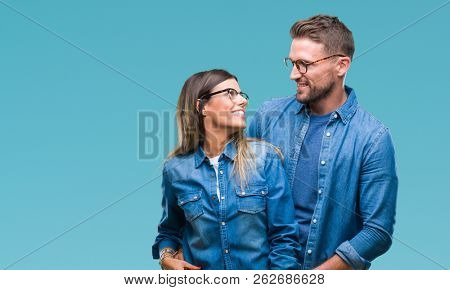 Young couple in love wearing glasses over isolated background looking away to side with smile on face, natural expression. Laughing confident.