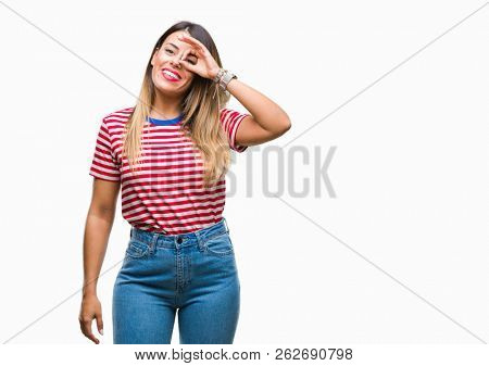 Young beautiful woman casual look over isolated background doing ok gesture with hand smiling, eye looking through fingers with happy face.