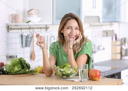 Woman Eating Vegetable Salad At Table In Kitchen. Healthy Diet