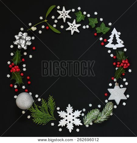 Abstract Christmas wreath garland with winter flora and bauble decorations on black background. Top view. Traditional festive Christmas card for the holiday season.