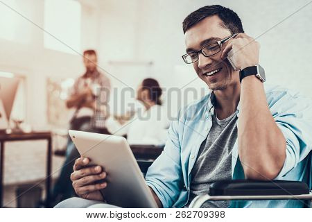 Man In Glasses On Wheelchair With Tablet Pc In Office. Disabled Young Man. Man On Wheelchair. Recove