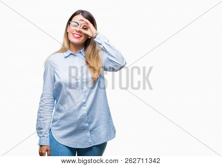 Young beautiful business woman wearing glasses over isolated background doing ok gesture with hand smiling, eye looking through fingers with happy face.