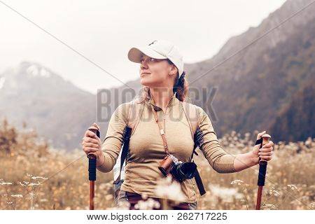 Happy Tourist With A Backpack And Trekking Sticks Goes And Enjoys Nature. Traveling Along The Mounta