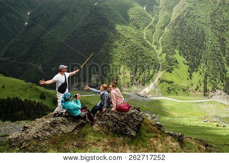 Group Of Friends Or Tourists Having Fun Enjoying Time Together At Mountains Viewpoint. Travel And To
