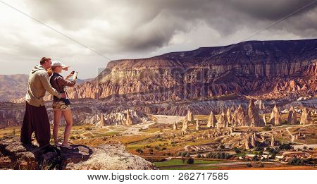 Couple Travelers With Camera Taking Photo Of Mountains Stand  At The Hill Of Goreme, Cappadocia, Tur