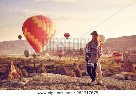 Couple Watching The Hot Air Balloons At The Hill Of Goreme, Cappadocia, Turkey. Cappadocia One Of Th