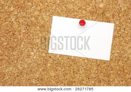 Blank business card with pushpin on corkboard