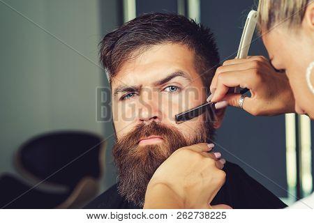 Barber Woman Shaving Client's Beard In Barbershop Or Beaty Salon. Portrait Of Male Client Shaving Hi