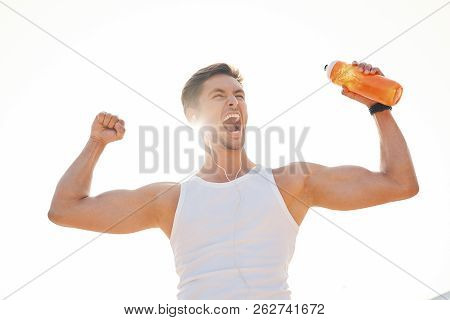 Athletic Muscular Man Feeling Victory And Enjoys Success Holding A Bottle Of Water. Emotion, Power,