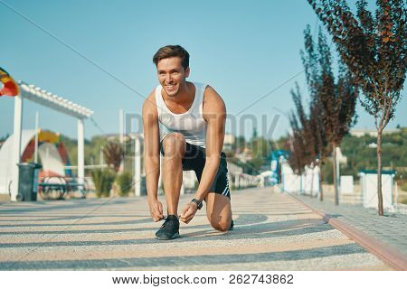 Smiling Young Male Runner Getting Ready To Start Running On A Sunny Beautiful Day With Sky In Backgr