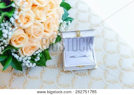 Beautiful Wedding Rings On Jewelry Box Lie On Light Surface Against Background Of Bouquet Of Flowers