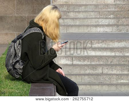 Teen Girl In Black Clothing Sitting Outdoor With A Smartphone. Concept For Social Networks, Online D