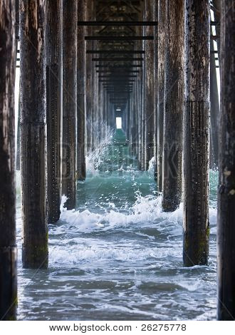 Waves crashing underneath a pier while the tide is rolling out.