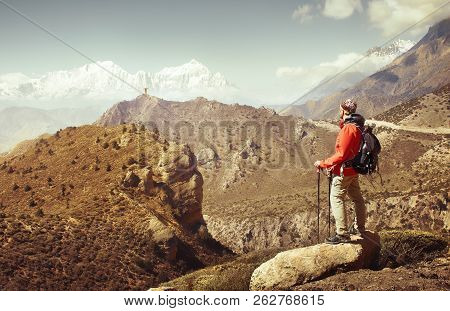 Hiker With Backpack Looks At The Beautiful Mountains In Upper Mustang, Annapurna Conservation Area,