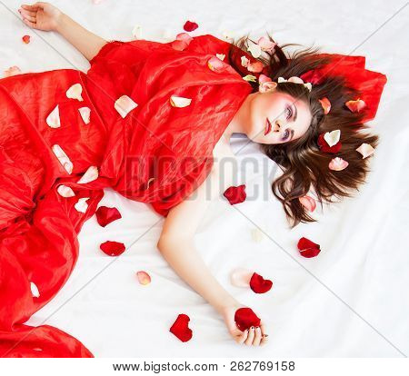 Portrait Of Beautyfull Sexy Girl With Long Hair Relaxing On White Linen Sheets With Rose Petals