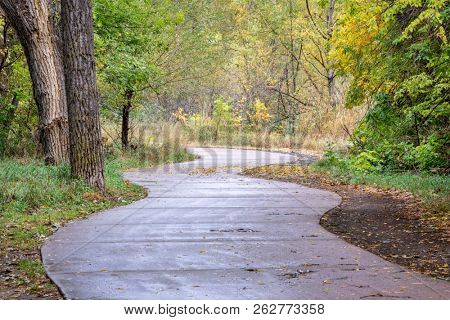 windy bike trail along the Poudre River in Fort Collins, Colorado - rainy day with fall colors