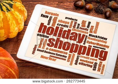 holiday shopping word cloud on a digital tablet with a pumpkin and gourd