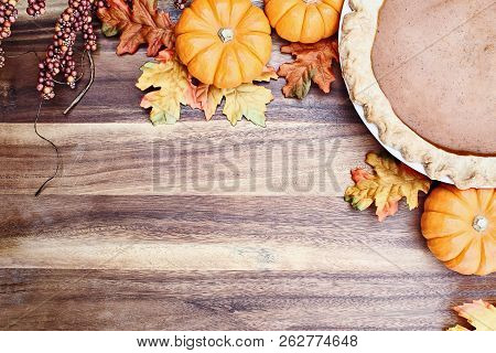 Homemade Pumpkin Pie In Pie Plate With Little Pumpkins, Autumn Leaves And Room For Text Over Rustic