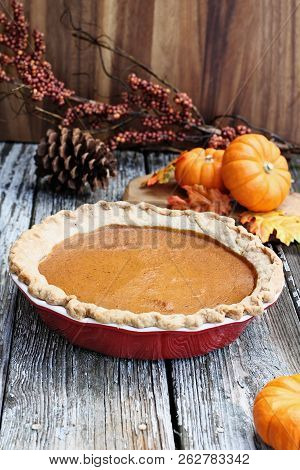 Homemade Pumpkin Pie In Red Ceramic Pie Plate Over A Rustic Wooden Background. Extreme Shallow Depth