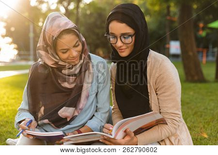 Photo of a happy young arabian women students writing in copybooks in park outdoors.
