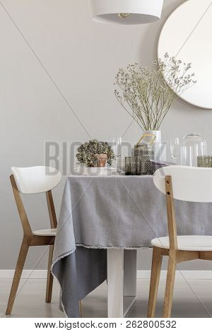 White Chairs And Laid Table In An Elegant And Pastel Dining Room Interior. Real Photo