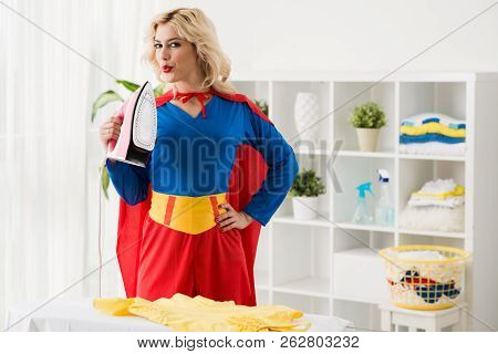 Portrait Of Young Attractive Blond Female Maid In Superwoman Costume Standing By Ironing Board With