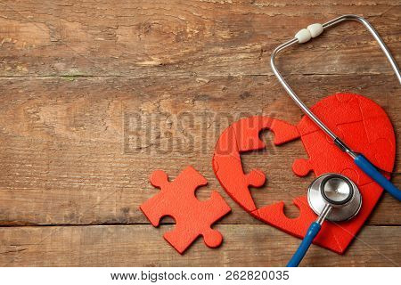 Heart Puzzle Red And Stethoscope On Wooden Background. Concept Diagnosis And Treatment Of Heart Dise