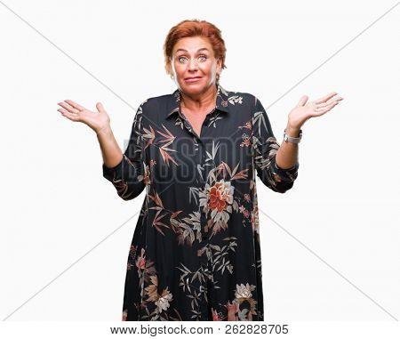 Atrractive senior caucasian redhead woman over isolated background clueless and confused expression with arms and hands raised. Doubt concept.