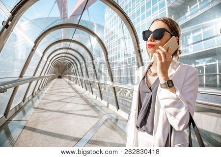 Portrait Of A Business Woman Talking With Phone On The Modern Covered Bridge At The Business Center