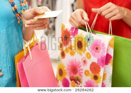 Close-up of woman?s hand holding credit card with another female near by during shopping