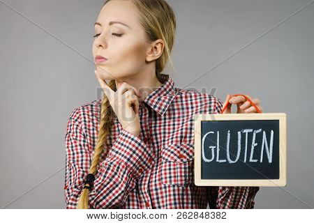 Thinking Woman With Braided Hair Holding Small Black Board With Gluten Sign. Bakery And Bread Allerg