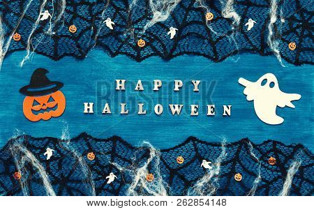 Halloween background. Happy Halloween letters and Halloween decorations on the dark blue wooden background, Happy Halloween festive concept, Halloween design