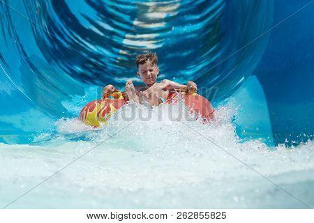 Boy Having Fun On The Water Slide On Floater In The Aqua Fun Park.