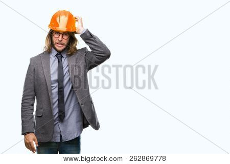 Young handsome architec man with long hair wearing safety helmet over isolated background confuse and wonder about question. Uncertain with doubt, thinking with hand on head. Pensive concept.