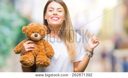 Young beautiful woman holding teddy bear plush over isolated background screaming proud and celebrating victory and success very excited, cheering emotion