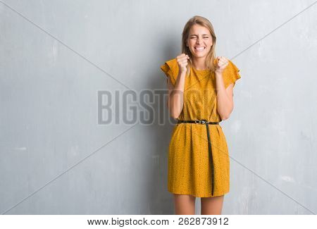 Beautiful young woman standing over grunge grey wall wearing a dress excited for success with arms raised celebrating victory smiling. Winner concept.