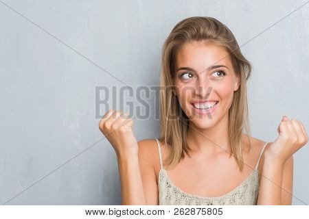 Beautiful young woman standing over grunge grey wall screaming proud and celebrating victory and success very excited, cheering emotion