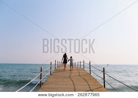 Mom And Son Walking Along The Pier. Sea Horizon And Blue Sky. Family Vacation At Sea. Summer Time Se