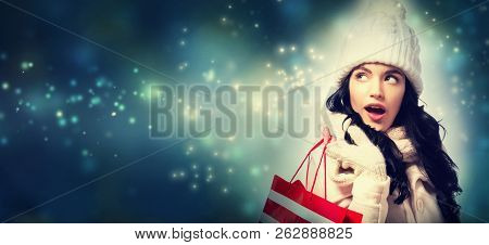 Happy Young Woman Holding A Shopping Bag In Snowy Night