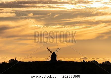 Mill silhouette under warm sunset, Ushant island, Brittany, France