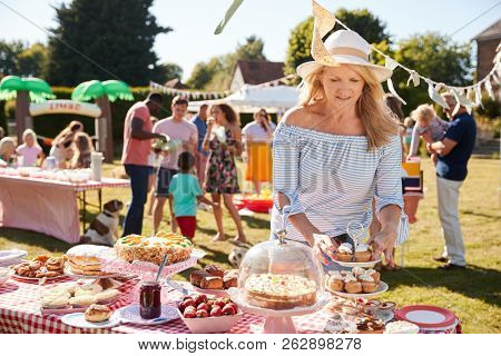 Mature Woman Serving On Cake Stall At Busy Summer Garden Fete